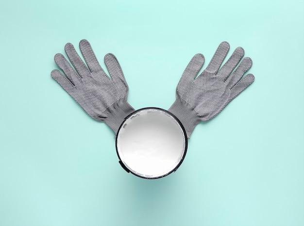Kreative komposition mit dose weißer farbe und arbeitshandschuhen auf pastellblau