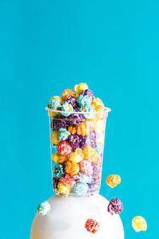 Kreative komposition mit farbigem popcorn in einem transparenten glas