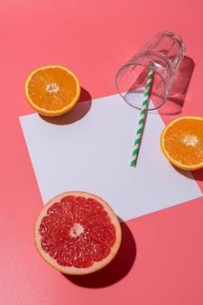 Kreative komposition mit früchten und glas auf rosa hintergrund mit harten schatten
