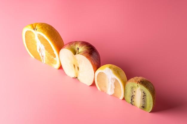 Kreative komposition mit geschnittenen früchten auf rosa hintergrund