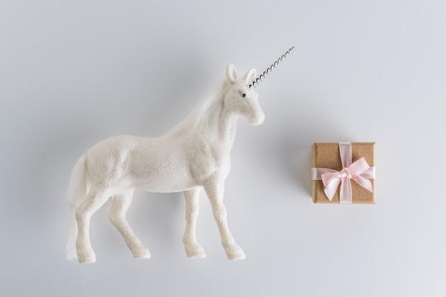Kreative komposition mit glitzer-einhorn und geschenkbox