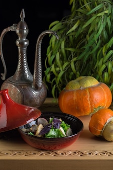 Kreative komposition mit kürbis, orientalischem krug und fertig zubereitetem frischem salat im studio. herbstkomposition