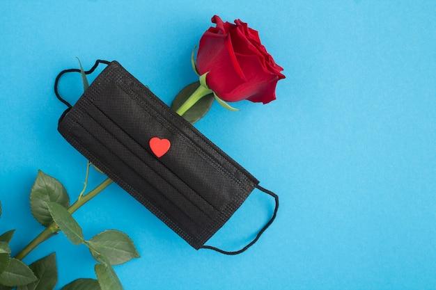 Kreative komposition mit roter rose und schwarzer medizinischer maske