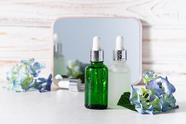 Kreative komposition mit zwei hautpflegeseren in glasflaschen auf weißem rustikalem hintergrund