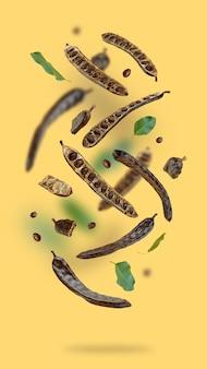 Kreative komposition schwimmende bio johannisbrotschoten samen blätter auf einem beige lebensmittel hintergrund natürlich