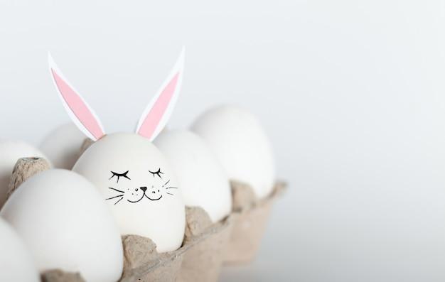 Kreative konzeptfotografie. weiße eier mit hasenohren und gesicht. frohes osterferienkonzept. minimalismus.