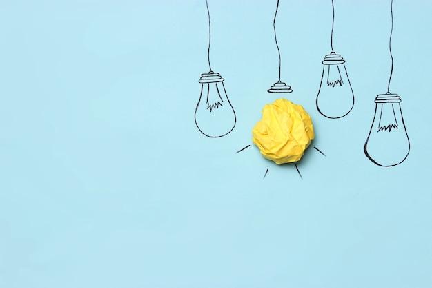 Kreative konzeptidee bemalte glühbirne mit einem zerknitterten gelben papierball