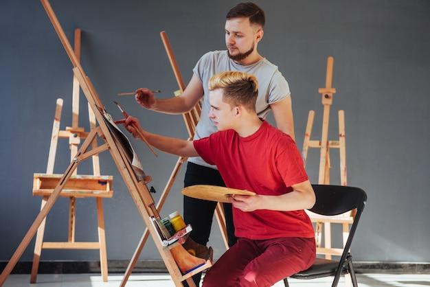 Kreative künstler haben im atelier ein buntes bild auf leinwand mit ölfarben gemalt