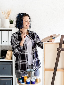 Kreative künstlerin, die ein bild malt, das in ihrem studio arbeitet