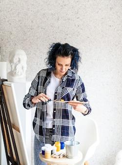 Kreative künstlerin, die ölfarben auf palette setzt, die in ihrem studio arbeitet