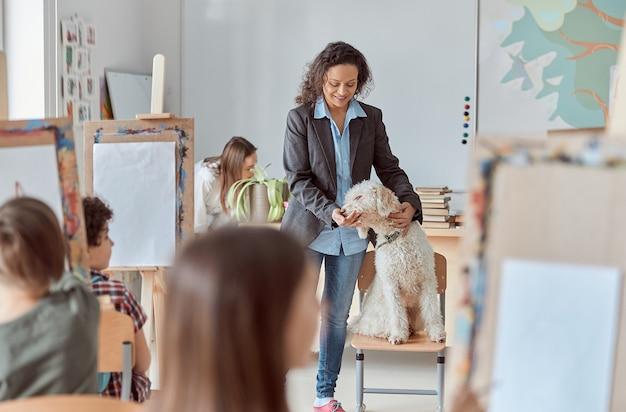 Kreative lehrerin zeigt einen hund zum zeichnen von kindern in einer gruppenstunde in der schule