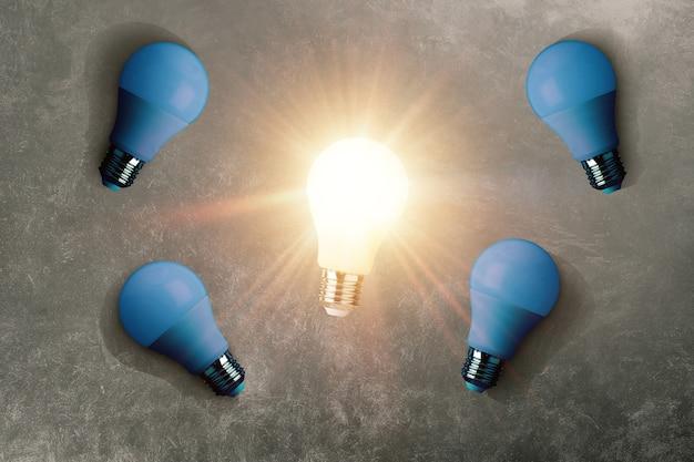 Kreative leuchtende glühbirne mit blauen glühbirnen auf konkretem hintergrund, draufsicht. denken sie anders, konzept. kreative idee und glühbirne