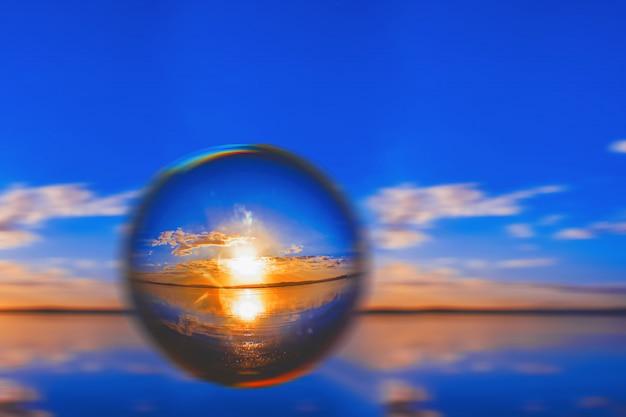 Kreative linsenballfotografie des sonnenlichts am horizont mit wolken herum im blauen himmel