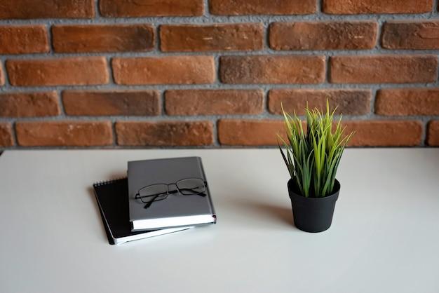 Kreative loft-backsteinmauer und zubehör des arbeitsplatzes auf weißem tisch. kopierraum, weicher selektiver fokus.
