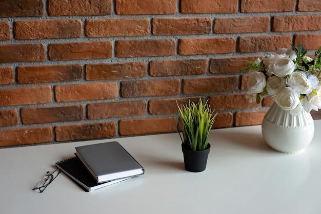 Kreative loft-backsteinmauer und zubehör des arbeitsplatzes auf weißem tisch