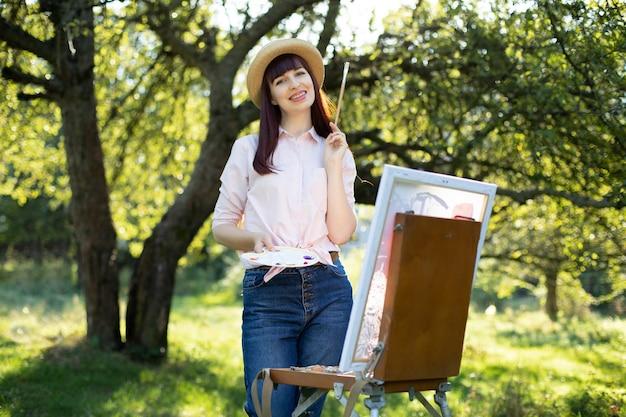 Kreative malerei, kunst, entspannung und inspiration. hübscher junger weiblicher künstlermaler, der bei sonnenuntergang im schönen frühlingsgrünpark oder -garten malt. junge frau mit pinsel zum malen auf leinwand.