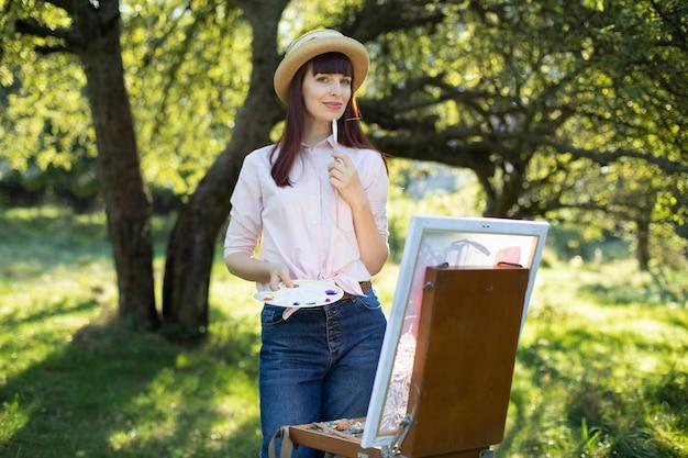 Kreative malerei, kunst, entspannung und inspiration. hübscher junger weiblicher künstlermaler, der bei sonnenuntergang im schönen frühlingsgrünpark oder -garten malt. outdoor-workshop in der natur.