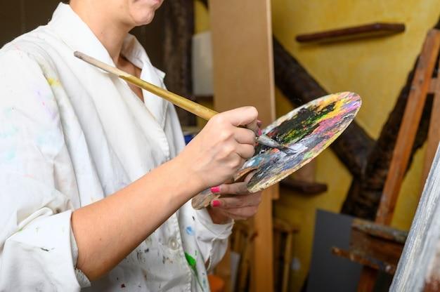 Kreative malerin mischt palette von ölfarben in paletten-nahaufnahme