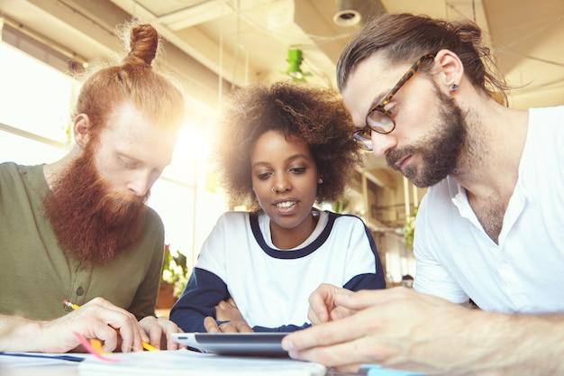Kreative menschen beim brainstorming beim treffen mithilfe des touchpads, um ideen und pläne zu notieren.