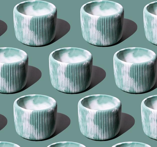 Kreative musterkomposition mit konkretem grünem und weißem blumentopf. auf grünem hintergrund. minimalismus. natürliches material. umweltfreundlich.