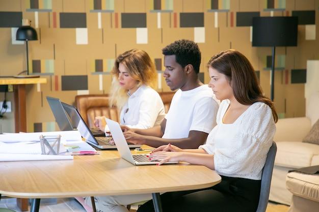 Kreative profis sitzen zusammen mit blaupausen am tisch und arbeiten am projekt