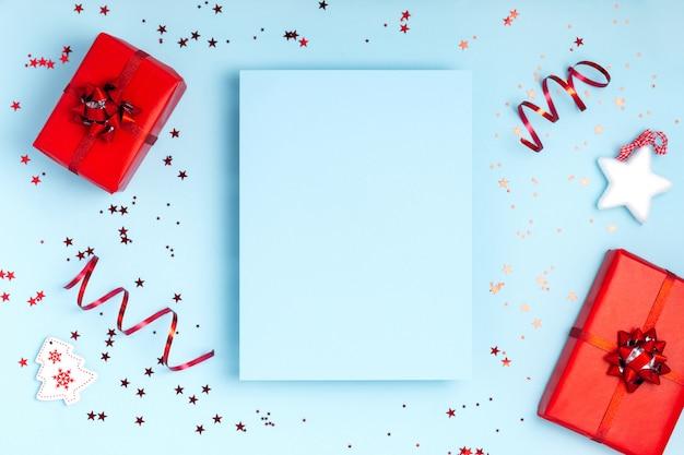 Kreative rahmenzusammensetzung des winters des neuen jahres und des weihnachten. leeres blatt papier, geschenkboxen und scheine auf blauem pastellhintergrund. draufsicht, flache lage, kopienraum. template design einladungskarte