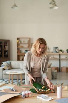 Kreative reife designerin der innenausstattung, die komposition aus grünen blättern und pflanzen macht und sie in holzrahmen setzt