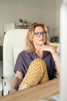 Kreative reife geschäftsfrau oder webdesigner, die computerbildschirm beim sitzen im sessel in der häuslichen umgebung betrachten