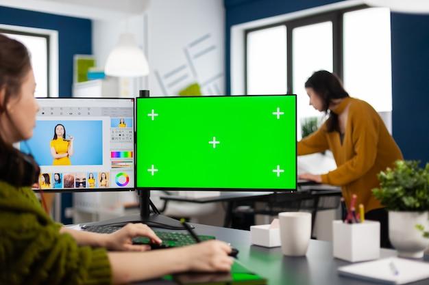 Kreative retuschierin, die assets im digitalen retuschierprogramm bearbeitet, konzentriert im fotoproduktionsstudio arbeitet und in computer mit grünem bildschirm schaut, chroma-key-mockup-isolierte anzeige