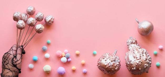 Kreative rosa papierflachlage, bannerkomposition. flaches layout mit glitzernden dekorativen metallkürbissen, weichen kugeln in pastellfarben und hand in schwarzem netzhandschuh mit dekorativen früchten