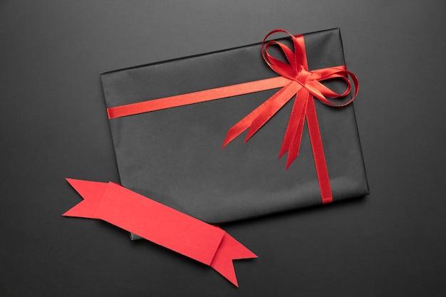 Kreative schwarze freitagkomposition mit geschenk