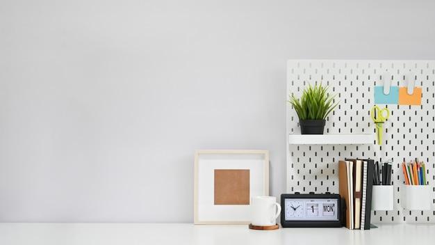 Kreative tabelle, bürozubehör mit kaffeetasse und fotorahmen auf weißem kopienraumschreibtisch.