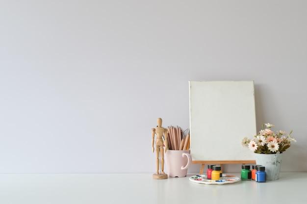 Kreative tabelle des büros mit versorgungen und weißer wand.