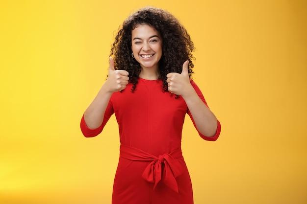 Kreative und charismatische, fröhliche, fröhliche frau 25s mit lockigem haar in rotem kleid, die zustimmend zwinkert und daumen mit breitem lächeln zeigt, zufrieden, positive antwort über gelbe wand zu geben.