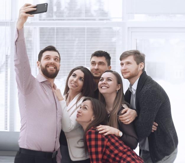 Kreative unternehmensgruppe macht selfies in einem modernen büro