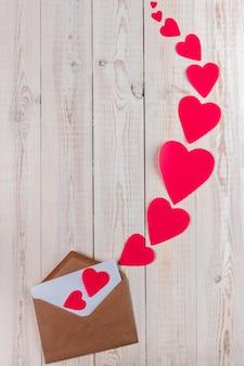Kreative valentinstagzusammensetzung, weißer hölzerner hintergrund mit umschlag und viele großen und kleinen roten herzen, valentinstagkonzept, ebenenlage, draufsicht, kopienraum