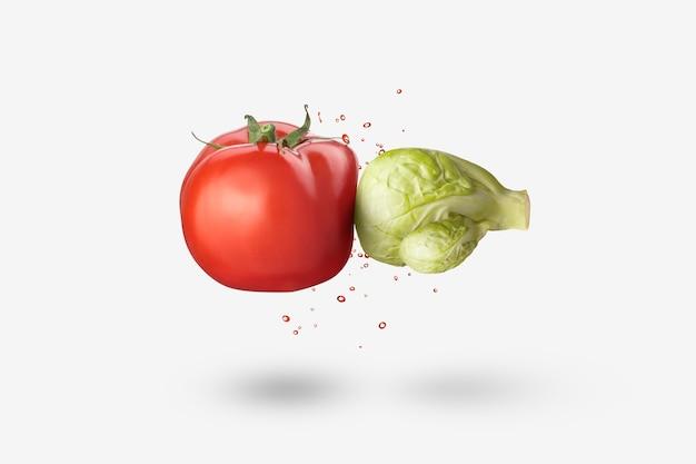 Kreative vegane komposition aus frischem, natürlichem bio-kohl in form von boxhandschuhen, die rotes tomatengemüse mit spritzer auf weißem hintergrund stanzen, kopierraum. veganes gesundes lebensmittelkonzept.