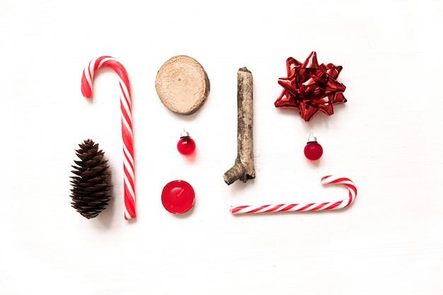 Kreative weihnachtsflachelagemischung mit kiefernkegeln, zuckerstangen, geschenkbogen, glaskugel