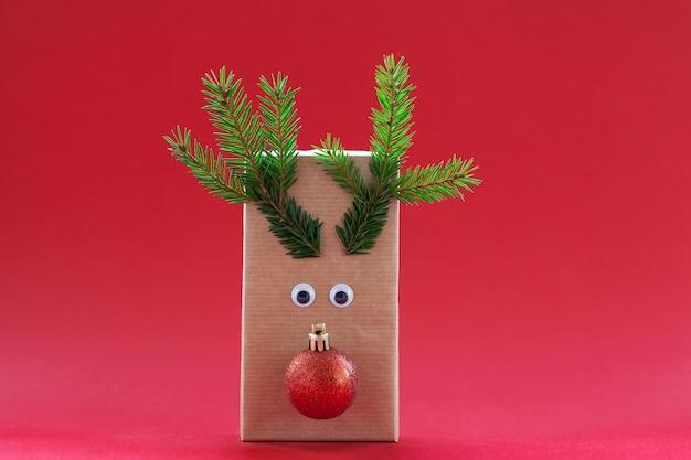 Kreative weihnachtsgeschenkbox in form des roten hintergrunds des santa rentiers.