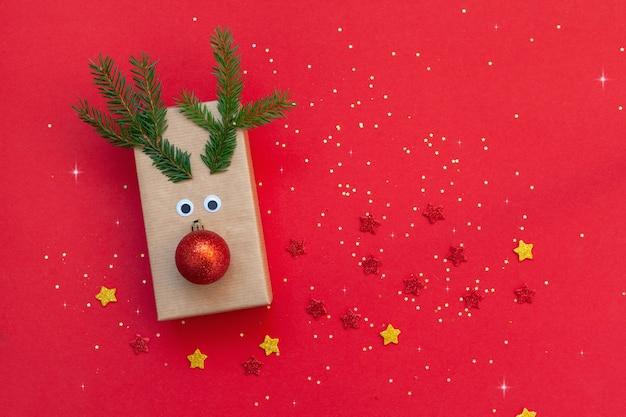 Kreative weihnachtsgeschenkbox in form eines hirsches auf rotem grund. feiertagsgrußkarte.