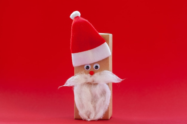 Kreative weihnachtsgeschenkbox in form von weihnachtsmütze und bart auf rotem hintergrund.