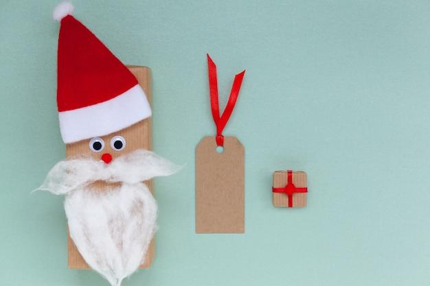 Kreative weihnachtsgeschenkbox in form von weihnachtsmütze und bart mit klarem etikett und geschenk auf blauem hintergrund. symbol für verkauf und einkaufen.