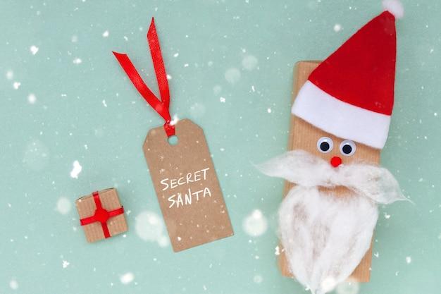 Kreative weihnachtsgeschenkbox in form von weihnachtsmütze und bart mit leerem tag und geschenk auf blauem hintergrund. geheimes santa-konzept.