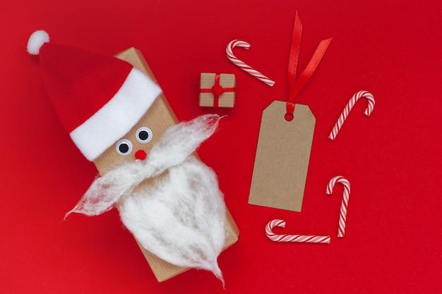 Kreative weihnachtsgeschenkbox in form von weihnachtsmütze und bart mit leerem tag und geschenk auf rotem hintergrund. geheimes santa-konzept.