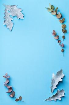Kreative weihnachtswinter-herbst-herbst-tageskomposition mit dekorativen getrockneten blättern. flache lage, draufsicht, kopienraum, stillleben blauer pastellhintergrund für grußkarten