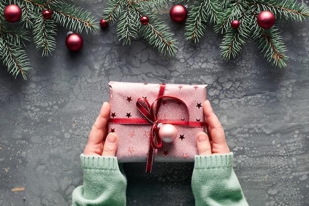 Kreative weihnachtswohnung lag auf grauer acrylflüssigkeitstafel. weibliche hände im grünen minzpullover, der geschenkbox hält, eingewickelt in rosa papier mit rotem band. feuer und stechpalmenzweige mit burgunderfarbenen farbkugeln.
