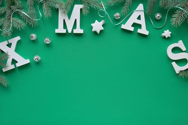 Kreative weihnachtswohnung lag mit großen weißen buchstaben weihnachten auf grünem textil, kopierraum. tannenzweige mit sternen verziert, spiegel discokugeln.