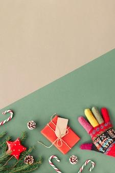 Kreative weihnachtswohnung legte hintergrund in grün und rot auf geteiltem grünem und handwerklichem braunem papier, kopienraum. geben sie verzierten wollhandschuh, zuckerstangen, verpacktes geschenk mit pappanhänger, sterne, tannenzweige ab.