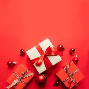 Kreative weihnachtszusammensetzung mit rotem präsentkarton, bändern, roten großen und bällchen, feiertagsdekorationen auf rot. flache lage, draufsicht, copyspace