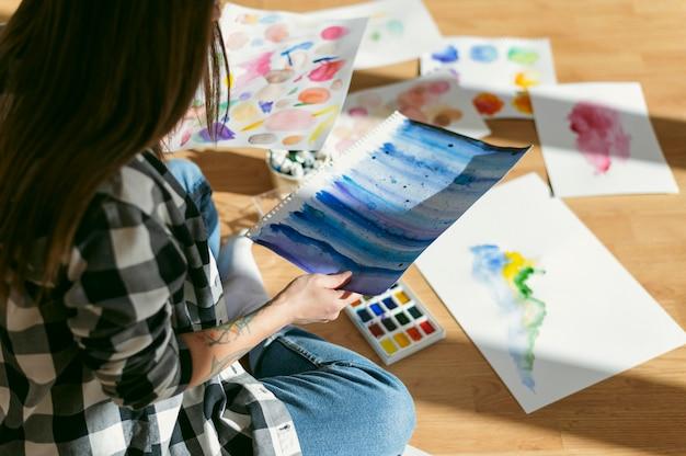 Kreative zeitgenössische malerin, die ihre zeichnungen auf den boden legt